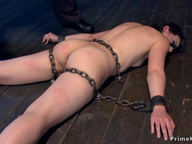 Laid and shackled slut gets whipped